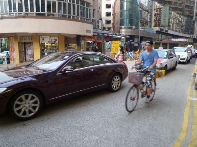 單車經過正在擠塞的汽車,攝於九龍金巴利道。